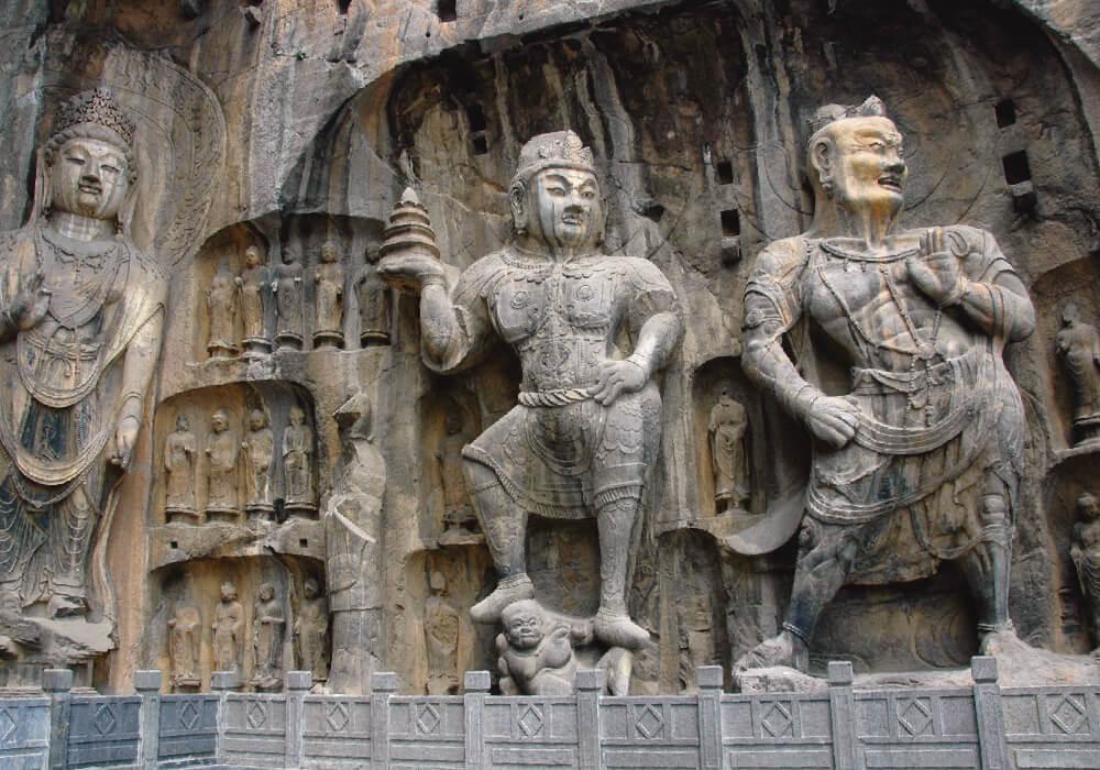 Grutas que contienen objetos budistas entre dos montañas.