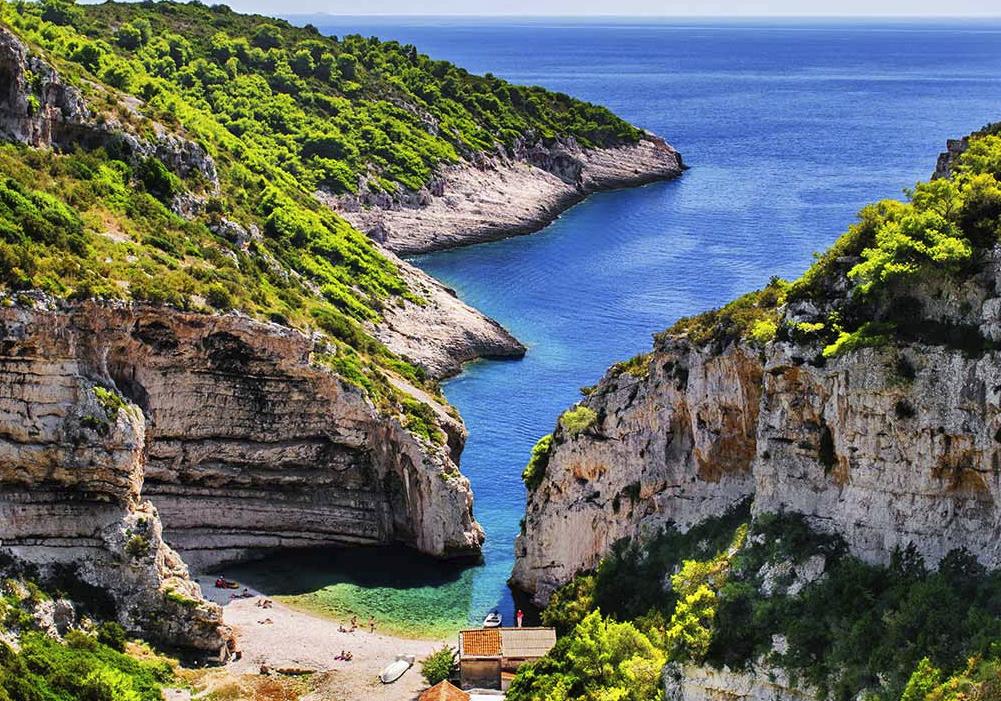 Ésta es una playa rodeada de vegetación y cercada por altas formaciones rocosas.