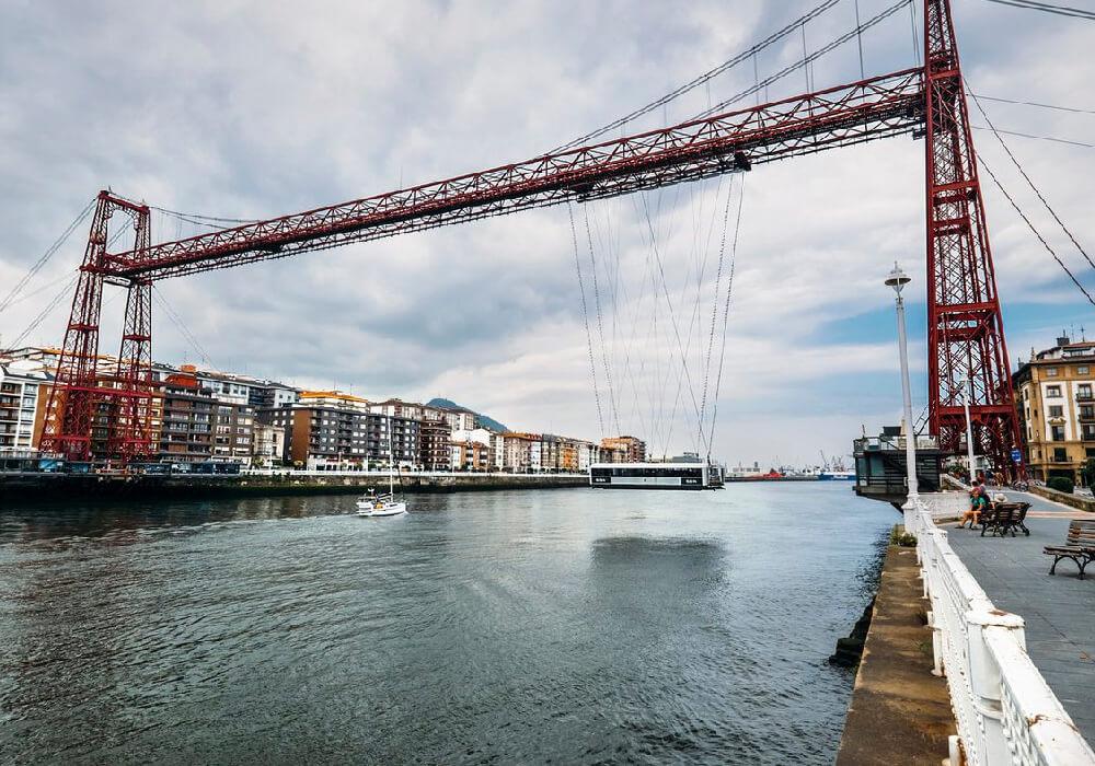 Es un puente colgante y transbordador de peaje.